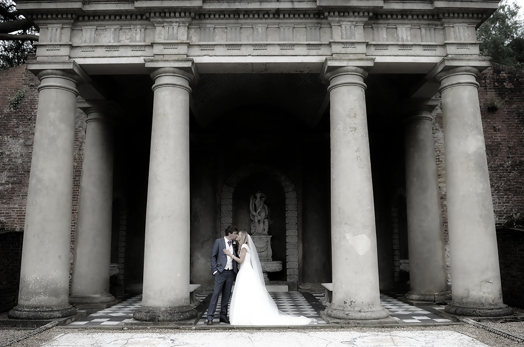 Magical wedding photograph of a beautiful Bride kissing her Groom at Wotton House in Dorking Surrey as they stand by the columns of the Roman Temple                                                                         at