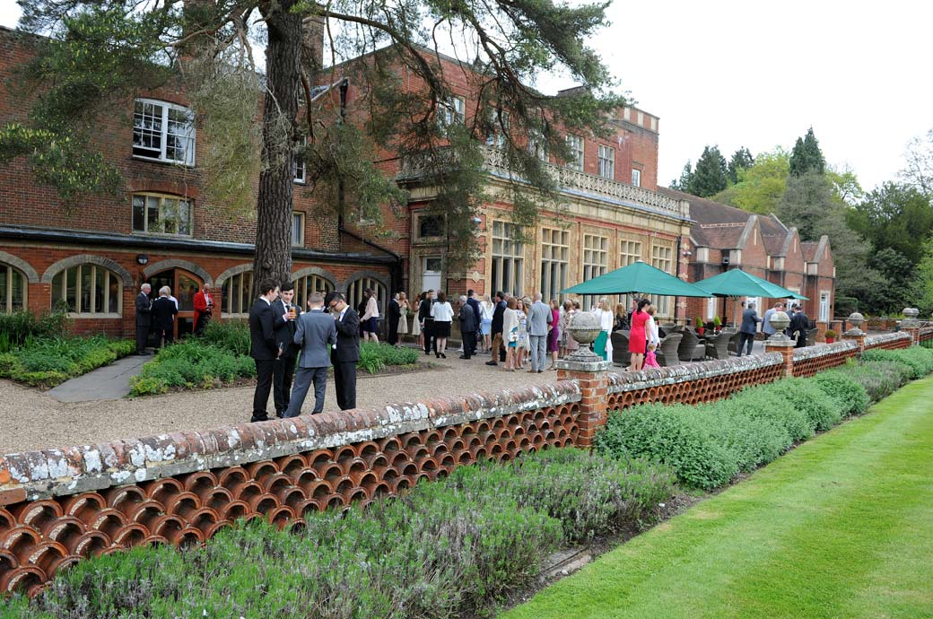 A long view wedding photograph taken from the lawn of guests having drinks on the terrace at the Wotton House wedding venue in Dorking Surrey