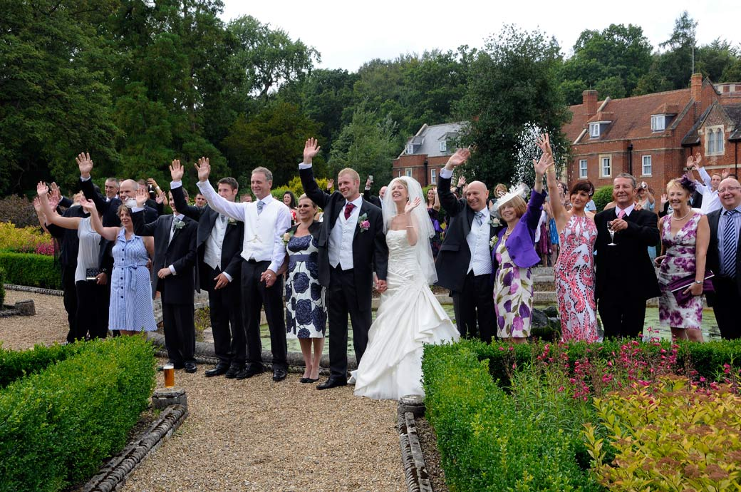 Close up wedding photo of happy guests standing around the fountain waving at the Surrey Lane wedding photographer at Wotton House Dorking