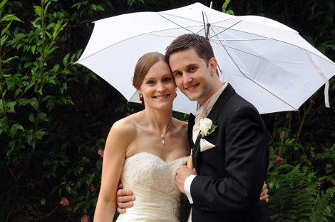 Happy Bride and Groom under a white umbrella wedding photograph taken on the drive at the picturesque Surrey wedding venue Ramster Hall Guildford