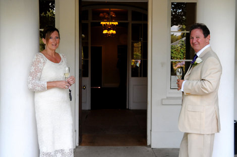 Relaxed Bride and Groom each with a glass of Champagne standing at the Pembroke Lodge  entrance wedding photo in Richmond Park Surrey wedding venue