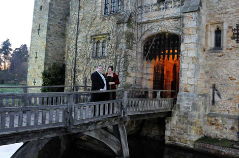 A celebrating couple standing on Hever Castle drawbridge wedding photograph taken at dusk at this picturesque and enchanting Kent wedding venue