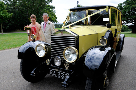 Happy couple in front of vintage yellow Rolls-Royce wedding photo taken at Merton Register Office in Morden Park House Surrey