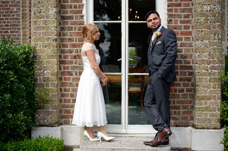 A fun wedding couple posing moment wedding photo captured outside the Sheridan Room at Merton Register Office Morden Park House