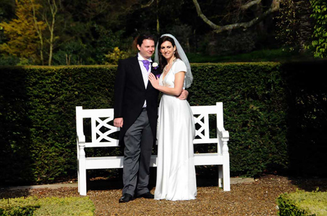 A happy Bride and Groom wedding photograph as they stand in the sun in the lovely Parterre garden at Clandon Park Guildford Surrey wedding venue