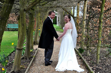 Happy Bride and Groom looking back wedding picture captured at the beautiful and elegant  Langshot Manor a boutique Surrey wedding venue