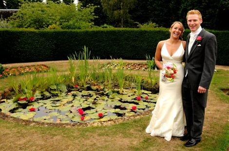A lovely relaxed wedding photo of the wedding couple laughing standing by the lilly pond captured at a Hartsfield Manor wedding reception