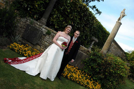 Happy newly-weds standing in the Italian Gardens wedding picture taken at the historic and magical Hever Castle a popular wedding venue in Kent