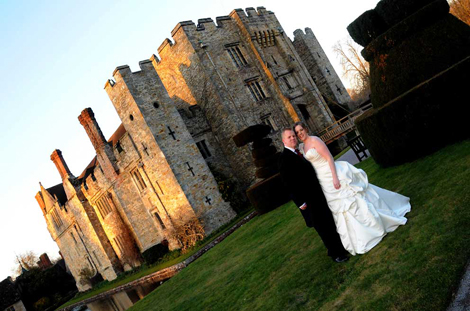 Happy newly-weds wedding photo taken as they stand in front of the picturesque Hever Castle in Edenbridge, a magical and enchanting Kent wedding venue