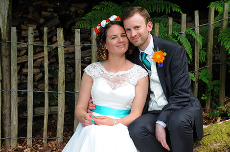 Happy smiling young newlywed couple captured in this wedding picture taken in Haslemere Surrey sitting down on a log by the woods taking time out to relax during the reception