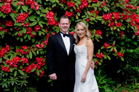 Newly married couple standing in front of the colourful Rhododendrons at the enchanting Kent wedding venue of Hever Castle