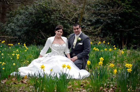 Lovely photo of a relaxed and content Bride and Groom sitting amongst the daffodils in the woods next to the Russell Suite at Pembroke Lodge, Surrey