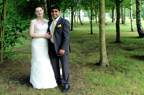 Loving couple standing by the trees in this romantic wedding photograph taken  on a copse near the fairway at Surrey wedding venue Shirley Park Golf Club