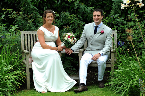 A lovely relaxed informal wedding picture of the newly-weds sitting on garden chairs in a beautiful private Surrey wedding venue in Hindhead