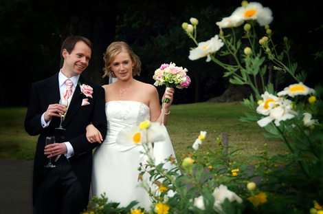 A happy Bride and Groom wedding picture as they stroll around the picturesque garden at Pembroke Lodge Richmond admiring the colourful summer blooms
