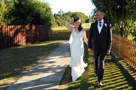 Radiant newly-weds wedding picture as they walk along the garden  at The Oaks Golf Centre  Centre in Carshalton a Surrey wedding venue