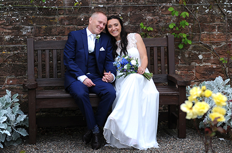 Wedding picture of a happy and relaxed Bride and groom as they take a rest on a garden bench captured a Surrey wedding photographer at Blaithwaite House in Wigton, Cumbria