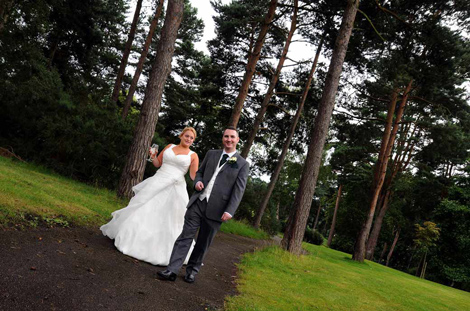 Happy Bride and Groom taking a romantic woodland walk wedding picture at Camberley Heath Golf Club wedding venue by Surrey Lane wedding photographers
