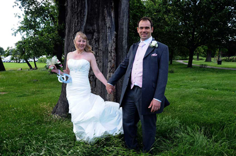 Smiling in the wind and trees couple wedding picture taken in Morden Park after a Merton Register Office Surrey wedding