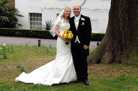 Smiling newly-weds picture taken on the grass in front of the Belvedere Suite at Pembroke Lodge Richmond Park Surrey wedding venue