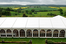 The view from the top of Surrey wedding venue Burrows Lea Country House in the village of looking down on the reception marquee and the stunning views of the Surrey Hills